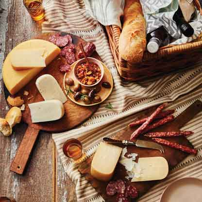 Overhead image of a variety of deli meats and cheeses on cutting boards with a bread basket.